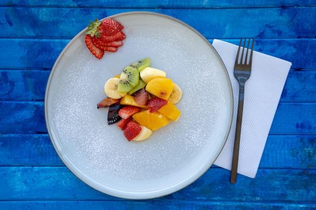 Insalata di frutta naturale e sana con arancia impostata in un piatto di presentazione gourmet su una superficie blu rustica.