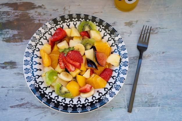 Insalata di frutta naturale e sana con arancia impostata in un piatto vintage, su una superficie rustica.