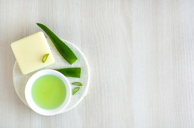 Prodotti a base di erbe naturali per la cura della pelle e la pulizia con l'aloe vera. vista dall'alto su ingredienti e cosmetici su legno bianco