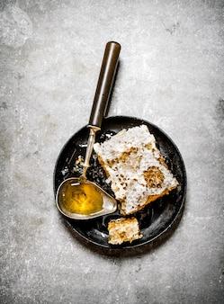 Miele naturale pettine con un cucchiaio vintage su uno sfondo di pietra