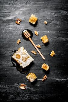Miele naturale in favo e un cucchiaio di legno. sulla tavola rustica nera.