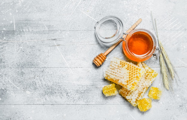 Miele naturale in favi. su fondo rustico.