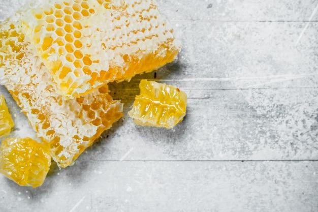 Miele naturale in favi. su una superficie rustica.