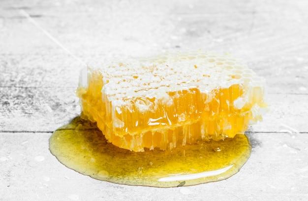 Miele naturale in favi. su un rustico.