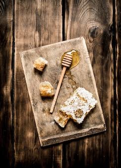 Miele naturale in favi con un cucchiaio sulla tavola su fondo di legno