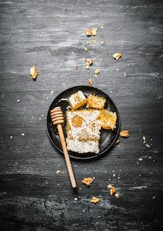 Miele naturale in favi con cucchiaio e noci. sulla superficie rustica nera.