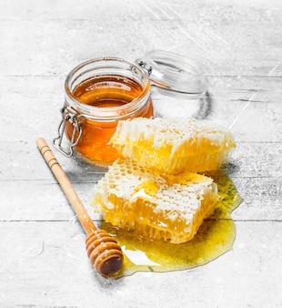 Miele naturale in favi con cucchiai di legno. su fondo rustico.