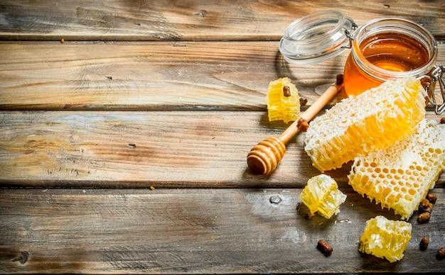 Miele naturale in favi. su una superficie di legno.