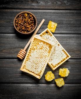 Miele naturale in favi su un tavolo di legno.