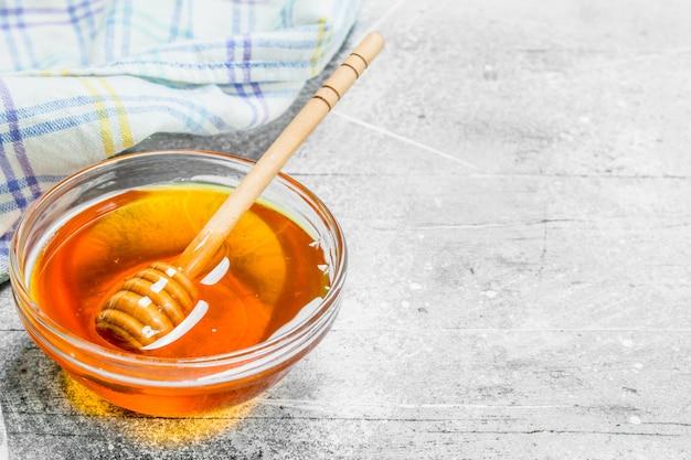 Miele naturale in barattolo con cucchiaio di legno. su fondo rustico.