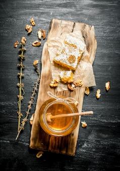 Miele naturale alle erbe. sulla tavola rustica nera.