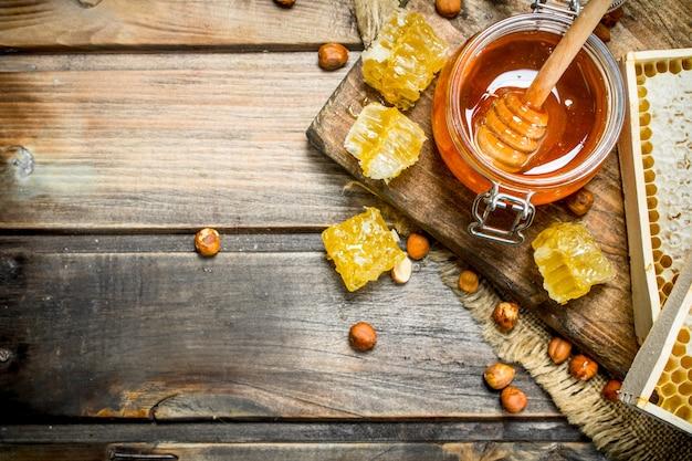 Miele naturale con noci. su uno sfondo di legno.