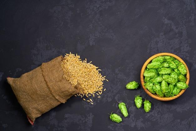 Ingredienti naturali per la produzione di birra, grano e luppolo su uno sfondo nero. malto d'orzo e coni di luppolo freschi verdi per birra artigianale su sfondo nero.