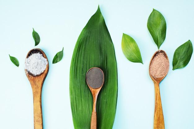 Foglie naturali accanto a rimedi popolari cosmetici per la cura della pelle. cucchiai di legno con argilla nera, rossa, arancione e grigia su una foglia di palma verde