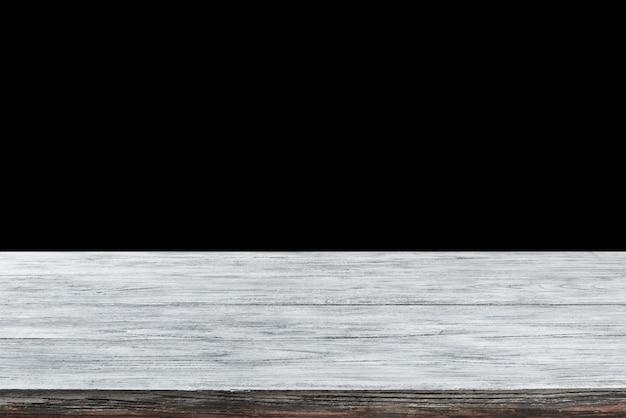 Tavolo vuoto strutturato in legno vecchio grigio chiaro naturale su sfondo nero. può essere utilizzato per la tua creatività o rappresentare i tuoi prodotti. utilizzato il focus stacking per creare una profondità di campo completa.