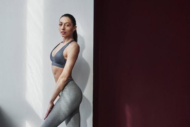 Illuminazione naturale. bella giovane donna con una bella forma del corpo fitness in posa nella stanza