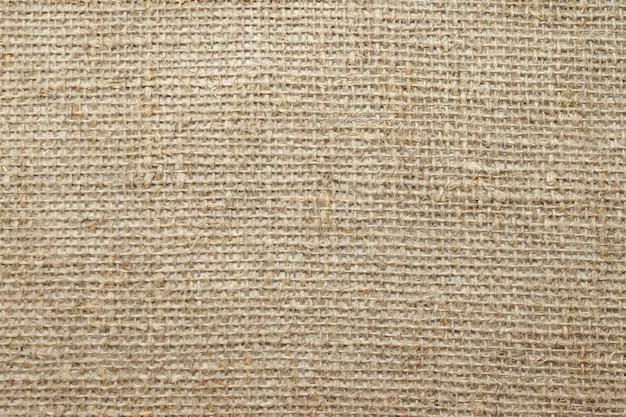 Tela di sacco in lino naturale grezzo non colorato. tela di tela di sacco della tela di iuta trama tessuta. avvicinamento. messa a fuoco morbida selettiva. . copia del testo spazio.