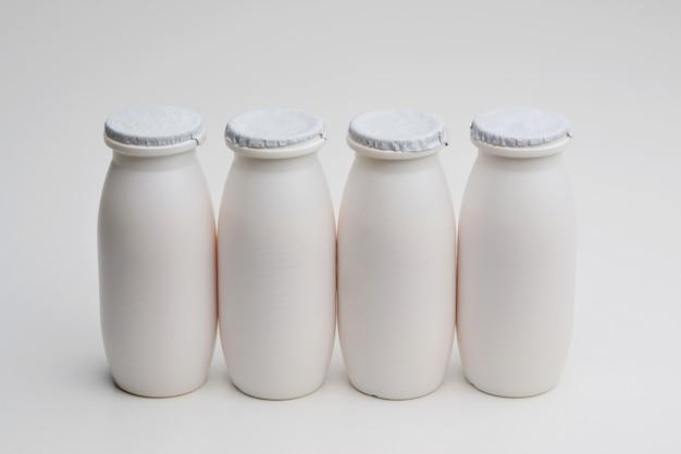 Yogurt liquido naturale con probiotici in piccole bottiglie di plastica su sfondo bianco