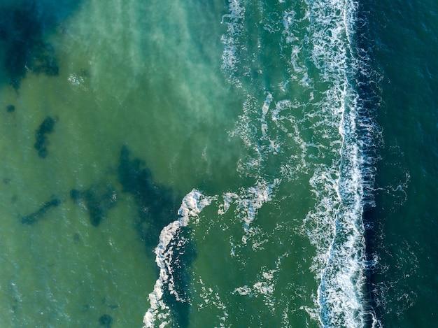 Paesaggio marino marino naturale con acque cristalline e profonde turchesi e onde di schiuma. vista aerea da drone. sfondo aqua con posto per il testo.