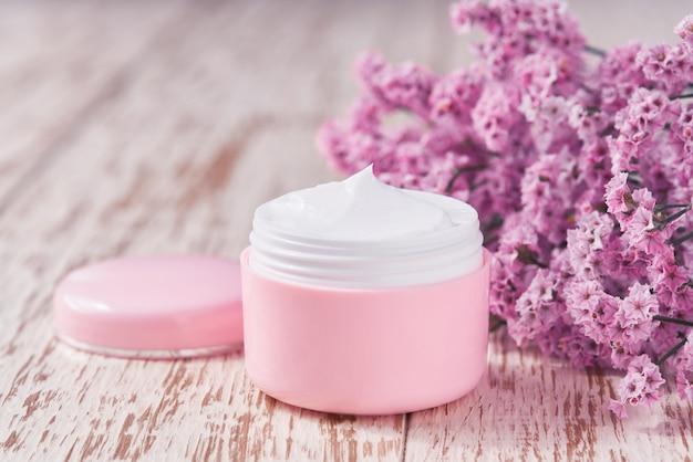 Crema idratante naturale o lozione per il corpo, concetto di cura della pelle antinvecchiamento su un tavolo di legno. vaso di plastica rosa per crema per la pelle sensibile su un tavolo di legno.