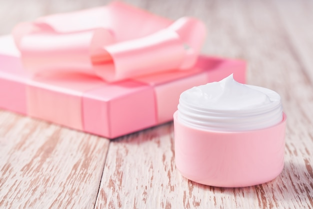 Crema idratante naturale o lozione per il corpo serie cosmetica di cosmetici idratanti e nutrienti di alta qualità. vaso di plastica rosa di cosmetici naturali su un tavolo di legno.