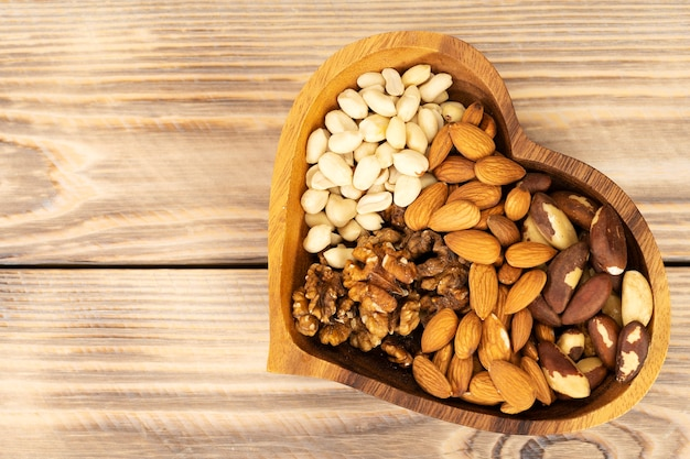 Miscela nutrizionale naturale di varie noci in un piatto di legno a forma di cuore su un tavolo di legno marrone