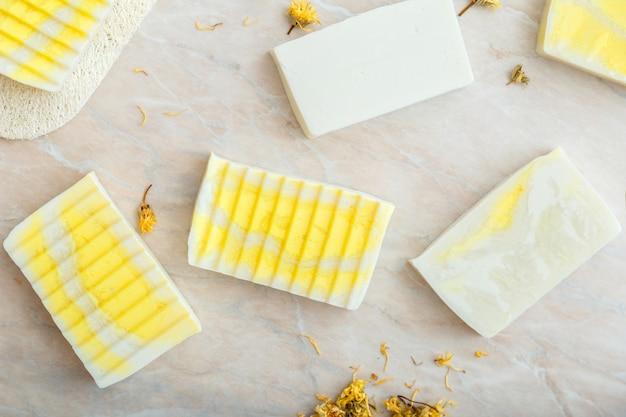 Modello di saponette di oliva naturale con fiori di calendula secchi di erbe. molti vari saponi bianchi fatti in casa, prodotti da bagno termali per la cura della pelle del corpo. articoli da toeletta per l'igiene piatti sul tavolo di marmo.