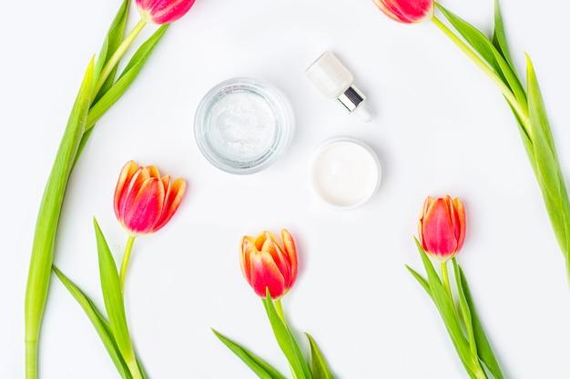 Concetto di cosmetici fatti in casa biologici naturali. prodotti per la cura della pelle, i rimedi e la bellezza: contenitori con crema e siero tra i fiori di primavera tulipano rosso su sfondo bianco. disteso, copia spazio per il testo