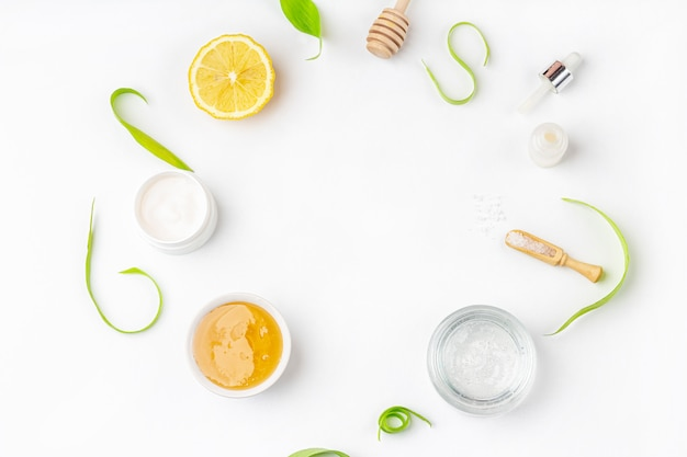 Ingredienti biologici naturali per la cura della pelle domestica. cosmetici detergenti e nutrienti. prodotti di bellezza: panna, miele, sale marino tra le foglie verdi distesi piatti, copia spazio per il testo