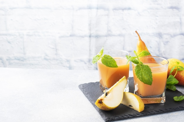 Succo di pera naturale in una tazza di vetro. succose conferenze mature pere e foglie di menta. copia spazio supporto di ardesia, sfondo chiaro di cemento.