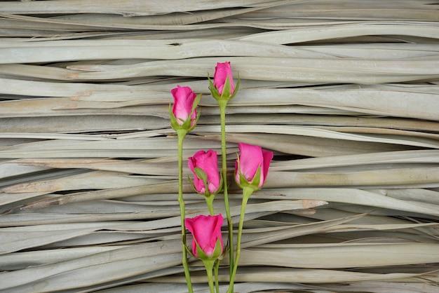Le rose rosa naturali piatte giacciono su sfondo di foglie di palma secche.