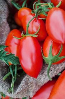 Concetto di prodotto naturale. pomodori prugna lunghi freschi in sacchetto di tela da imballaggio. pomodori sulla tavola di legno