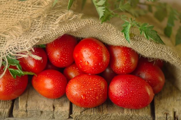 Concetto di prodotto naturale. pomodori prugna lunghi freschi in sacchetto di tela da imballaggio.
