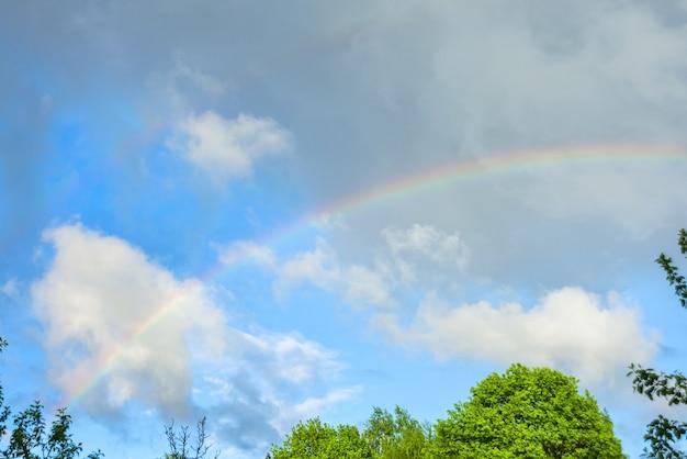 Arcobaleno naturale contro il cielo blu e nuvole piovose