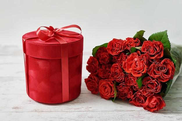 Rose rosse naturali e confezione regalo. biglietto di auguri di san valentino.