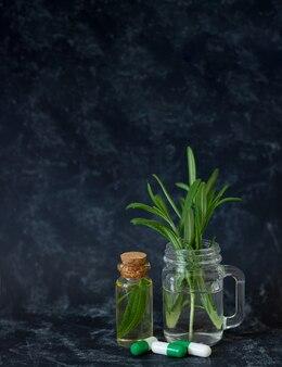 Olio essenziale di rosmarino naturale, foglie fresche e capsule a base di erbe per bellezza e spa su sfondo scuro con spazio di copia