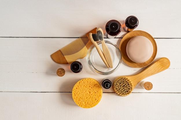 Siero naturale, sapone secco, spugne e spazzola per il massaggio del viso con setole naturali su un tavolo. presentazione di prodotti di bellezza spa ecologici biologici in ambiente naturale con colori neutri