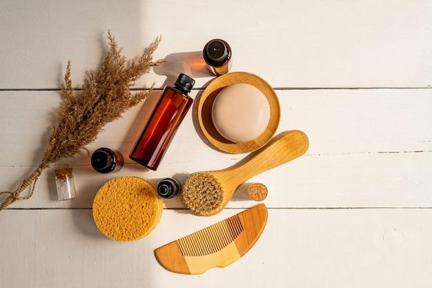 Siero naturale, sapone secco, spugne e spazzola per il massaggio del viso con setole naturali su un tavolo. presentazione di prodotti di bellezza spa ecologici biologici in un ambiente naturale dai colori neutri.