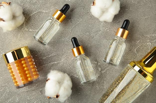 Cosmetico di bellezza per la cura della pelle naturale con ramoscello di cotone sulla superficie grigia