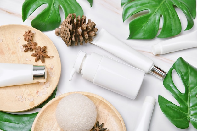 Prodotto di bellezza naturale per la cura della pelle, confezione di contenitori per bottiglie cosmetiche con foglie di natura verde, etichetta vuota per mock-up di marchio biologico spa, cura della pelle sana alle erbe