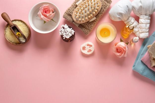 Prodotti cosmetici per la cura della pelle naturale su sfondo rosa pastello.