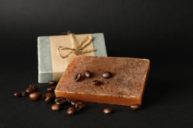 Sapone naturale e semi di caffè su sfondo nero