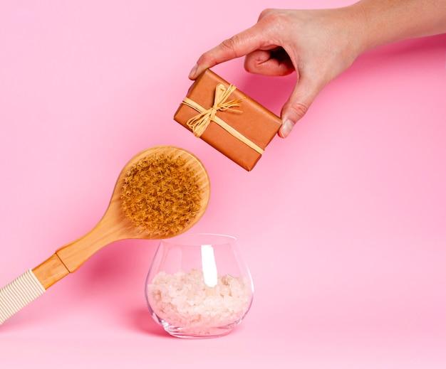 Sapone naturale in una mano femminile, sale marino, una spazzola di legno per massaggio a secco su sfondo rosa. concetto di cura del corpo. copia spazio. avvicinamento
