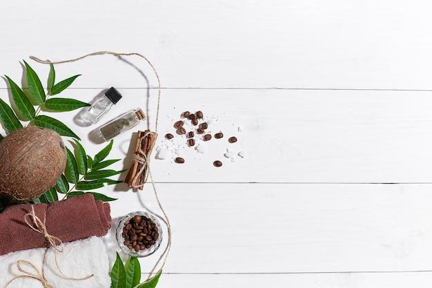 Set spa naturale con chicchi di caffè cannella sale marino olio asciugamano marrone cocco e foglie verdi su briciolo