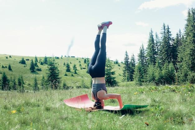 Naturale, sport, salute, persone, concetto di stile di vita - giovane praticante di yoga femminile indipendente in buona salute, praticando la meditazione e pone una bella vista serena della montagna che si affaccia sulla purezza