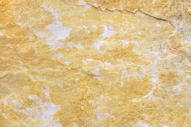 Texture di sfondo in pietra naturale con toni beige, gialli e grigi
