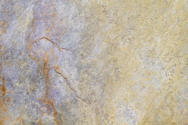 Texture di sfondo in pietra naturale con toni gialli, beige e viola
