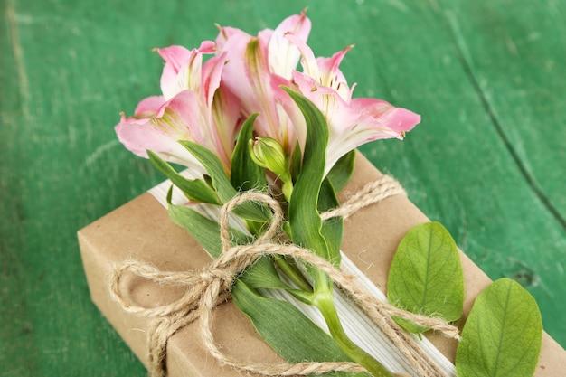 Scatola regalo artigianale in stile naturale con fiori freschi e spago rustico, su spazio in legno