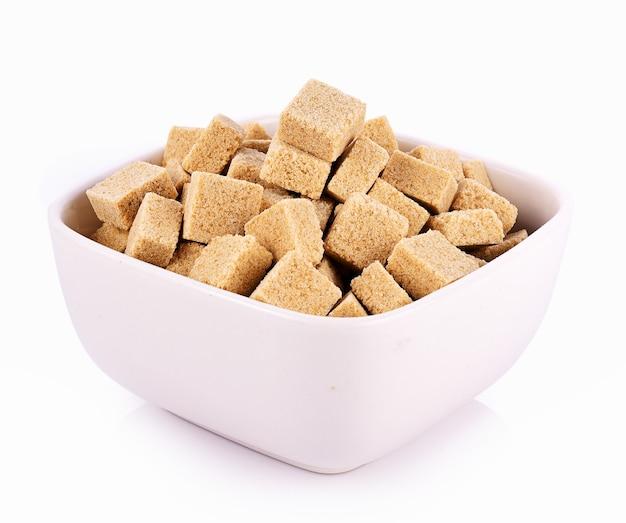 Zollette di zucchero naturale in ciotola su sfondo bianco