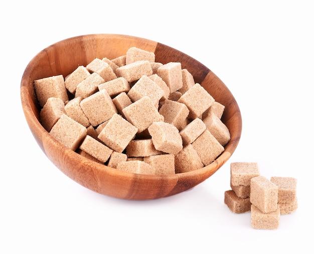 Cubetti di zucchero naturale in ciotola di legno su sfondo bianco